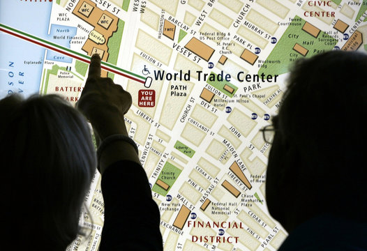 A woman points to at a map at the World Trade Center Path Station in New York