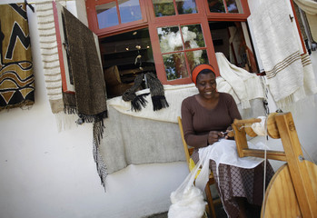 An African women weaves silk in the traditional way at a shop in the picturesque old part of Stellenbosch