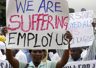 Nigerian workers hold placards during the World May Day celebrations in Nigeria's capital Lagos