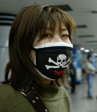 CHINESE COMMUTER WEARS A MASK DESIGNED WITH A SKULL IN SHANGHAI.