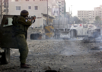 An Israeli soldier takes aim at Palestinian protesters during clashes in the West Bank city of Ramal..