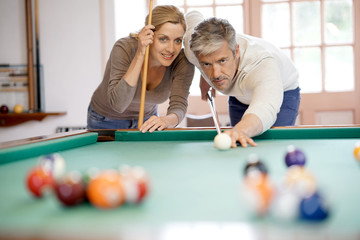 mature couple playing pool together