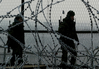 SOLDIERS PATROL INSIDE THE BARBED-WIRE FENCE AT IMJINKAK IN PAJU.