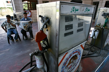 A Palestinian working at a gas station reads the newspaper as the pumps run empty in Gaza City