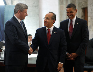 Canada's PM Harper shakes hands with Mexico's President Calderon as U.S. President Obama looks on during a trilateral meeting in Guadalajara