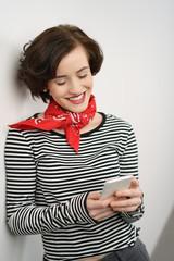 frau schaut lachend auf ihr mobiltelefon