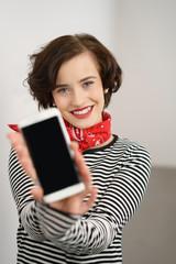 frau zeigt den display ihres mobiltelefons