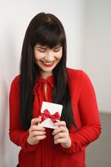 frau mit roter bluse freut sich über ein geschenk
