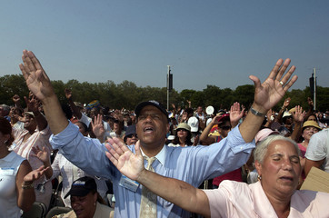 Followers pray before the start of Billy Graham's New York Crusade at Flushing Meadows Park.