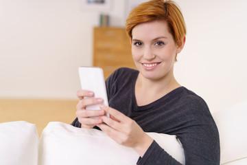 junge frau mit mobiltelefon auf dem sofa zu hause