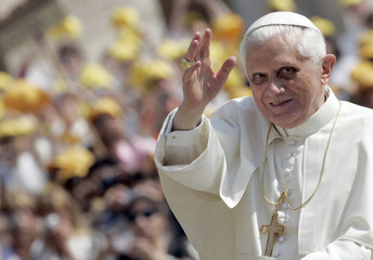 Pope Benedict XVI waves as he arrives to lead his weekly general audience in Saint Peter's square at the Vatican