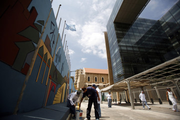 University art students paint a wall set up last month by the security forces of the United Nations headquarters in Beirut