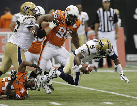 BC Lions'  Hunt and teammate Johnson sack Winnipeg Blue Bombers' Glenn during their CFL game in British Columbia