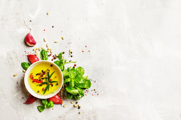 Food background, olive oil, cedar nuts, spices and herbs, green basil and garlic, flat lay