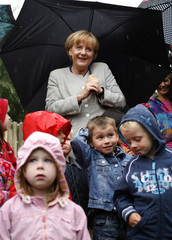 German Chancellor Merkel poses with children during a visit at a kindergarden in the western city of Hiddenhausen