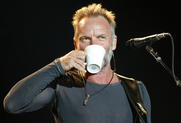The Police lead singer Sting drinks from a cup during a performance in Belgrade