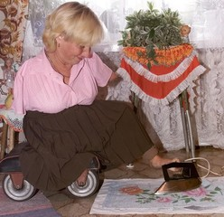 Invalid Lyubov Lukyanova irons a towel with her only leg at her flat in the village of Bely Yar.