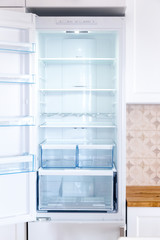 Opened new empty fridge with shelves and drawers for meat and vegetables.