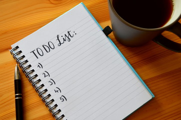 TO DO LIST handwritten on notepad on desk