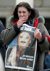 A woman cries as she holds a picture of murdered German fashion designer Moshammer at Munich's ...