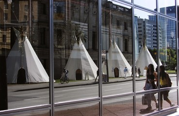 NATIVE TEEPEES SET UP FOR ABORIGINAL DAY REFLECTED IN VANCOUVER OFFICE TOWER.