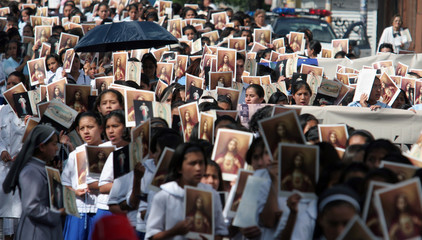 Catholics hold images of the sacred heart of Jesus as they march toward the Basilica to ask for peaceful elections in Mexico city