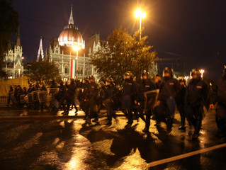 Riot police move in front of the parliament building in Budapest