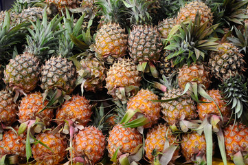 Ripe pineapple fruit pile on market table. Ready to sale.