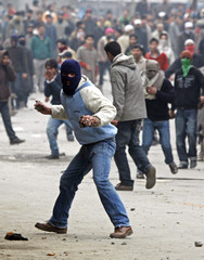 Masked Kashmiri protester throws stones towards Indian policemen during protest against Israel in Srinagar