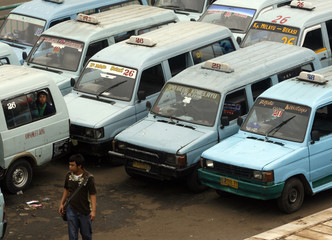 The 1990s model of the Toyota Kijang used for public transportation is parked along a Jakarta street as it waits for passengers