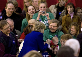 U.S. Democratic presidential candidate, Senator Hillary Clinton signs the shirt worn by baby during a campaign stop in Eldridge, Iowa