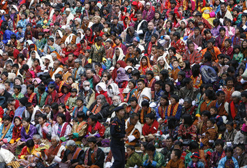 People wait before a traditional dance during the annual Tsechu festival in Paro