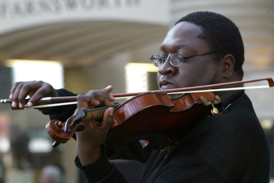 Man plays violin as visitors view body of Civil Rights activist Parks at Charles H. Wright Museum of African American History in Detroit