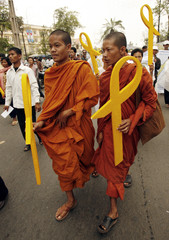 Cambodian Buddhist monks hold symbols for freedom in Phnom Penh