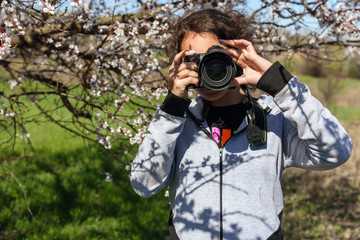 Girl with a camera on a background of flowering trees