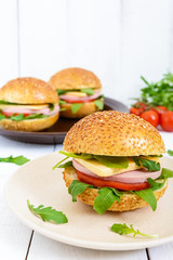Burgers with sausage, cheese, tomato, arugula and soft bun with sesame seeds on a white wooden background. Vertical view