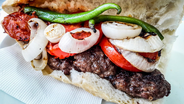 Turkish Kofte Ekmek / Meatball Sandwich with tomatoes, onion and green pepper.