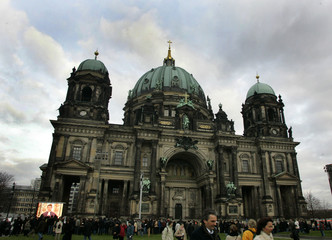 People stand outside the Berlin Cathedral during an Ecumenical church service to commemorate the ...