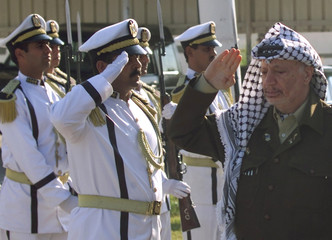 PALESTINIAN PRESIDENT YASSER ARAFAT SALUTES AN HONOUR GUARD AFTER ARRIVING IN GAZA.