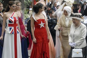 Britain's Queen Elizabeth and Turkey's First Lady Gul walk past models in Bursa