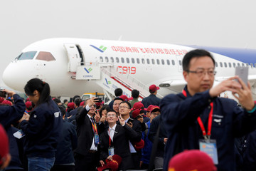 Attendees take photos in front of a Chinese C919 passenger jet after its first flight at Pudong International Airport in Shanghai