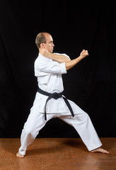 On a black background, the master trains karate blocks