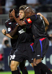 Juninho of Olympique Lyon celebrates with team mates after scoring during the Champions League match ...