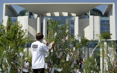 """Activist of movement """"Your Voice against Poverty"""" ties wish lists on bamboo trees in front of chancellery in Berlin"""
