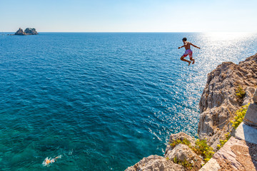 A boy is jumping from the cliff. Holidays in Montenegro