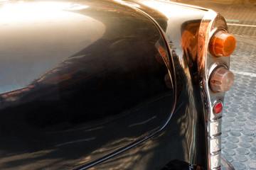 Close up back view of black old vintage car or automobile back side with back light. Back side of vintage car concept.