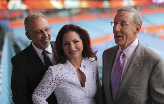 Music producer Emilio Estefan, his wife singer Gloria and Miami Dolphins team owner Stephen Ross pose for pictures during an event at the LandShark stadium in Miami