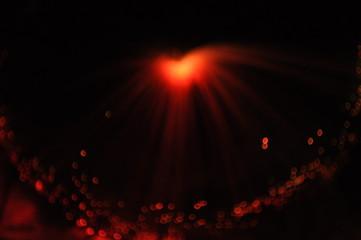 Shining orange heart on a black background