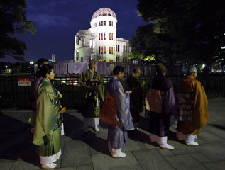 Buddhist monks walk past the gutted Atomic Bomb Dome on the way to a memorial service for the victims of the atomic bombing of Hiroshima