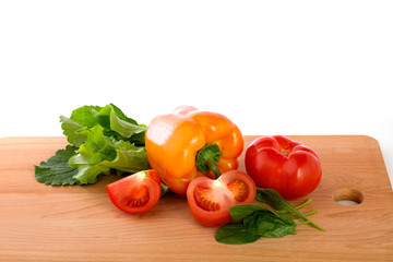 Fesh tomatoes and pepper on the wooden background